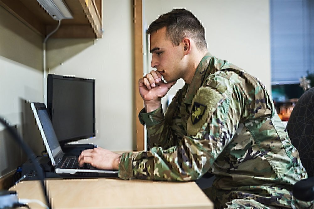 military man at desk with laptop